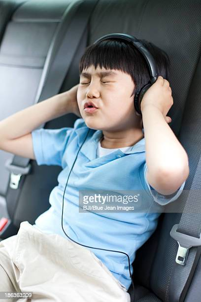 Cute boy listening to music and singing in car