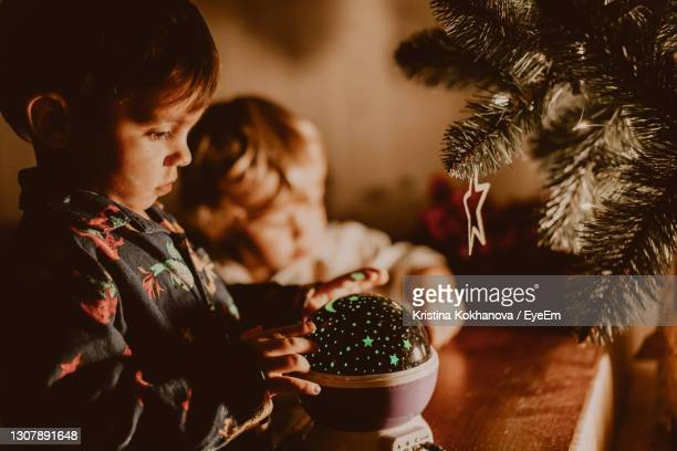 cute boy looking at christmas decoration at home - incidental people photos et images de collection