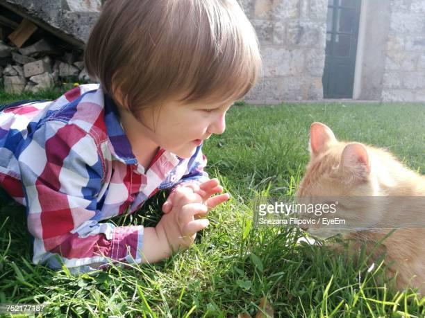 Cute Boy Looking At Ginger Cat In Grassy Field At Yard
