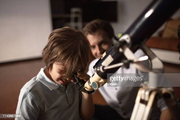 cute boy looking at sky through telescope with his father - telescope stock pictures, royalty-free photos & images