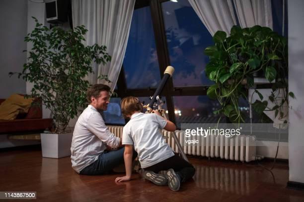 ragazzo carino che guarda il cielo attraverso il telescopio con suo padre - astronomia foto e immagini stock
