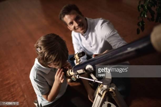 cute boy schaut bei sky durch teleskop mit seinem vater - astronomie stock-fotos und bilder