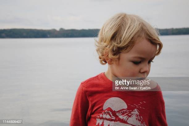cute boy looking away against sea - brianne stock pictures, royalty-free photos & images