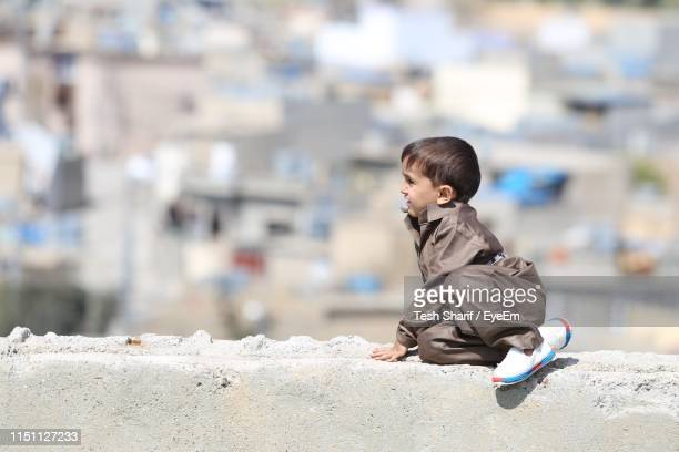 cute boy looking away while sitting on retaining wall in city - イラク ストックフォトと画像
