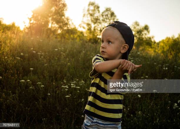 cute boy looking away while standing by plants on field - igor golovniov stock pictures, royalty-free photos & images