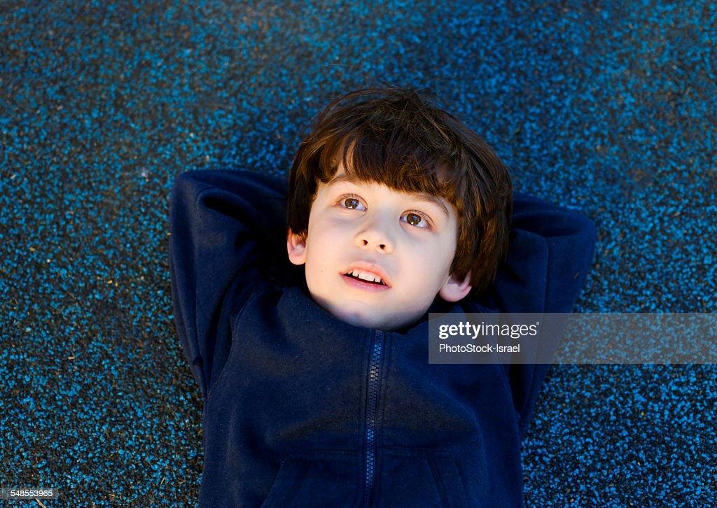 Cute boy lying on back gazing upward : Stock Photo