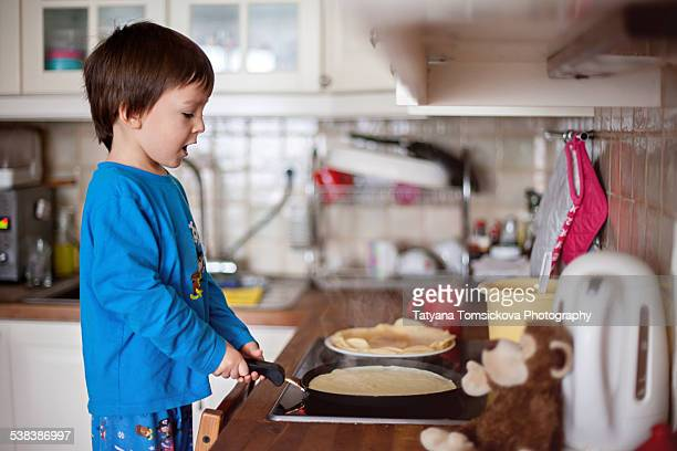 Cute boy, making pancakes at home