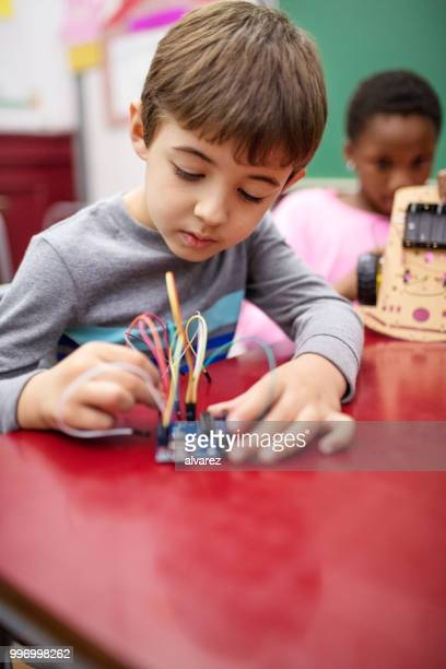 Cute boy making science project in classroom