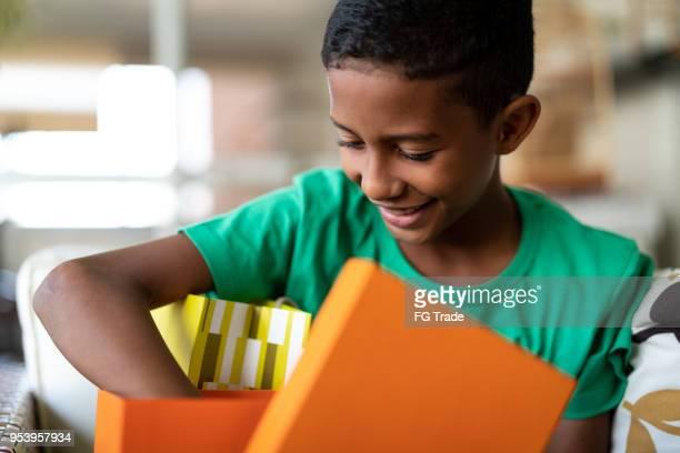 menino bonito, abrindo presentes - dia das crianças - caixa de presentes - fotografias e filmes do acervo