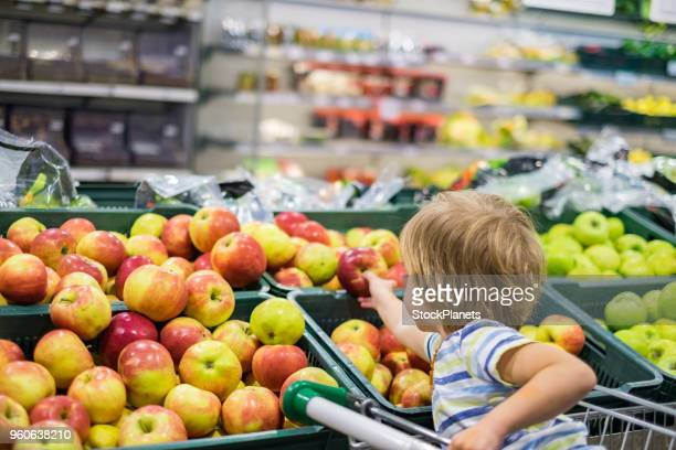 cute boy picking apple in the store - apple fruit stock pictures, royalty-free photos & images
