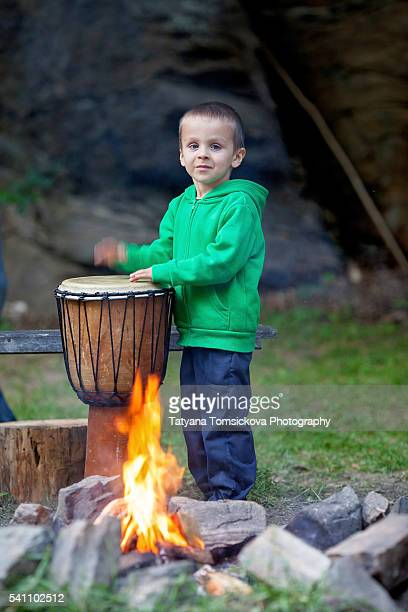 Cute boy, play on musical instruments around a camp fire