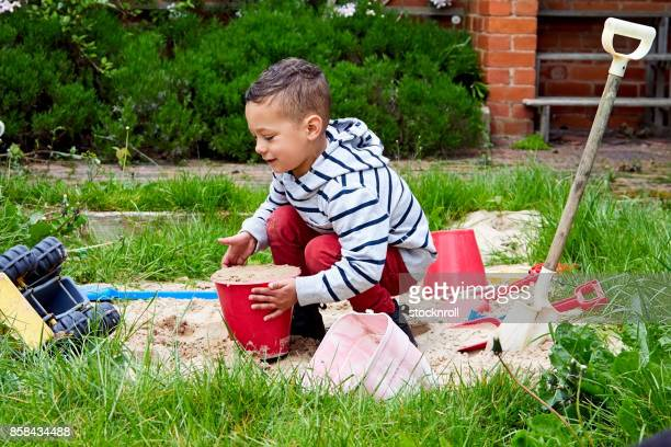 Cute boy playing in a sandbox in backyard