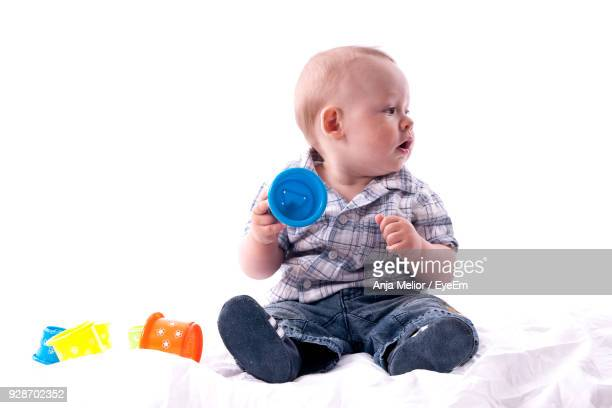 Cute Boy Playing On Bed Against White Background