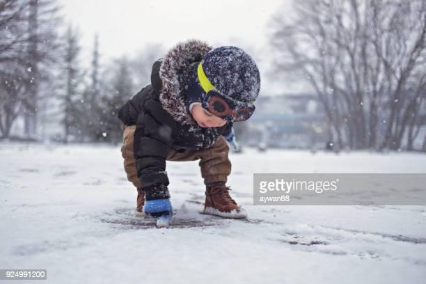 外で雪の中で遊ぶかわいい男の子 - first occurrence ストックフォトと画像