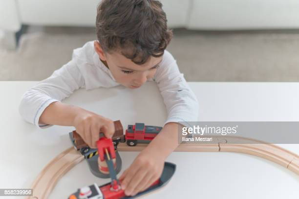 Cute boy playing with a wooden train