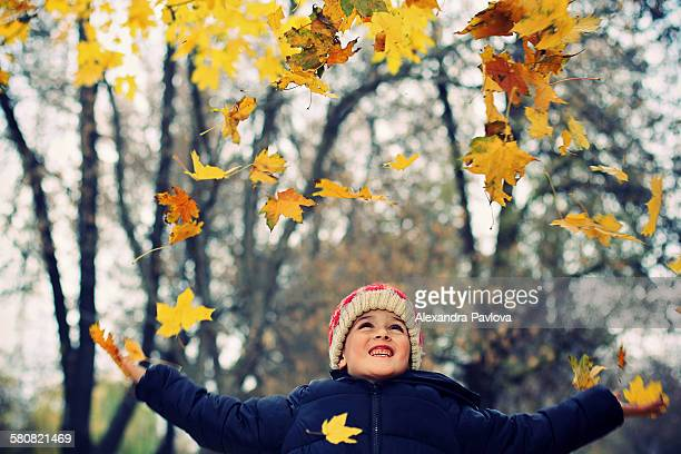 cute boy playing with autumn leaves
