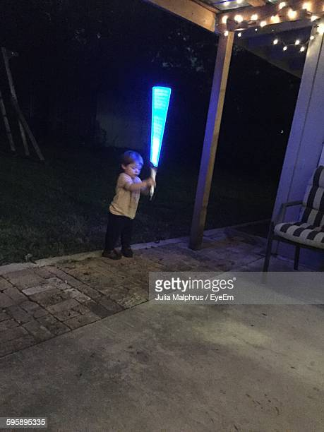 Cute Boy Playing With Laser Sword In Yard At Night