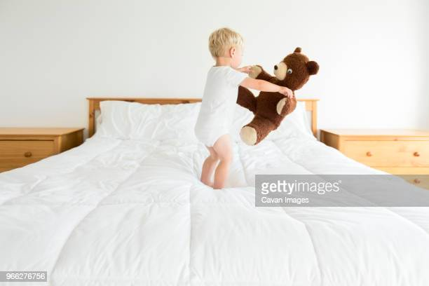 cute boy playing with teddy bear while standing on bed - dancing bear immagine foto e immagini stock