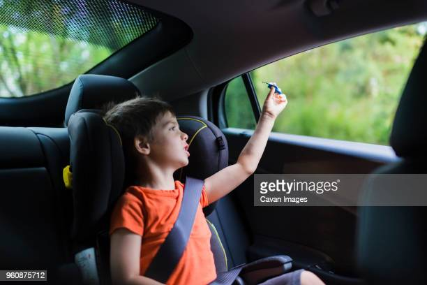 Cute boy playing with toy rocket on back seat of car