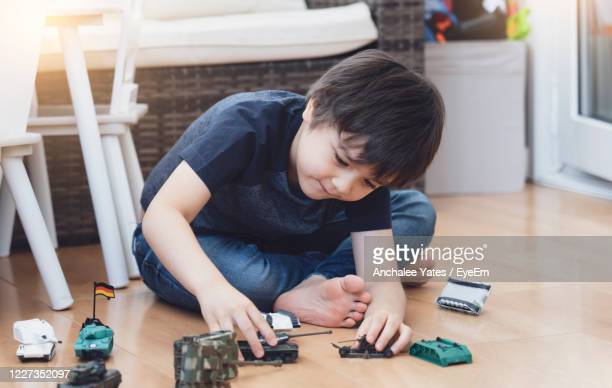 cute boy playing with toys on floor at home - primary age child stock pictures, royalty-free photos & images