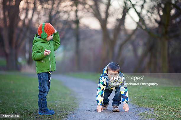 Cute boy, prepared for a start in a running competition, his younger brother holding a stop watch
