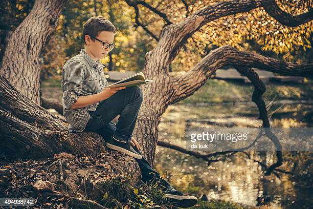 Cute boy reading a book in the park