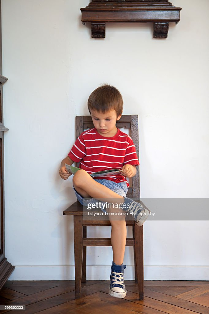 Cute boy, reading a book, sitting on vintage chair : Stock Photo