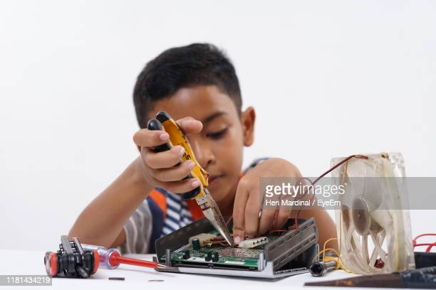 cute boy repairing electrical equipment on table against white background - heri mardinal stock pictures, royalty-free photos & images