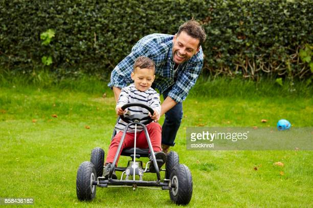 Cute boy riding pedal car with father in garden