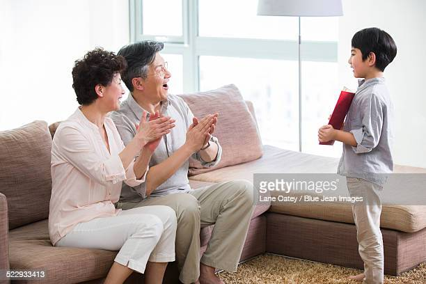 Cute boy showing certificate of merit to grandparents