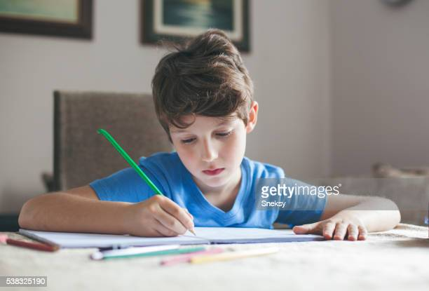 Cute boy sitting at the table doing his homework.