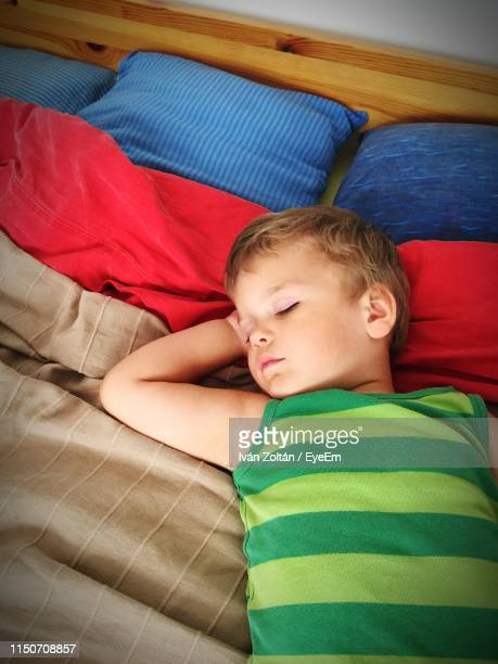 cute boy sleeping on bed at home - iván zoltán stock pictures, royalty-free photos & images