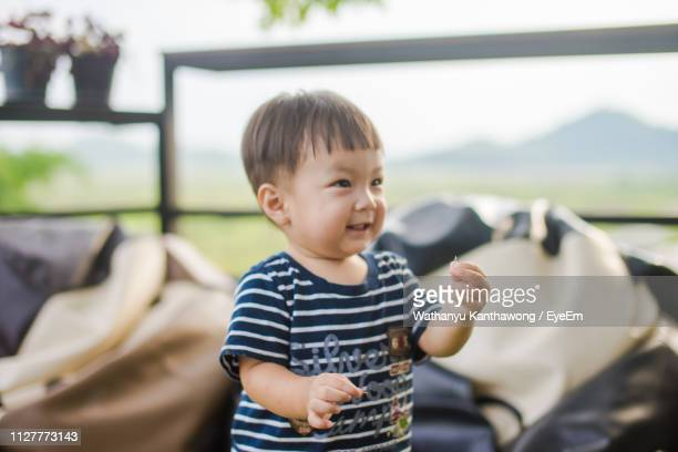 cute boy smiling while looking away at home - at home ストックフォトと画像