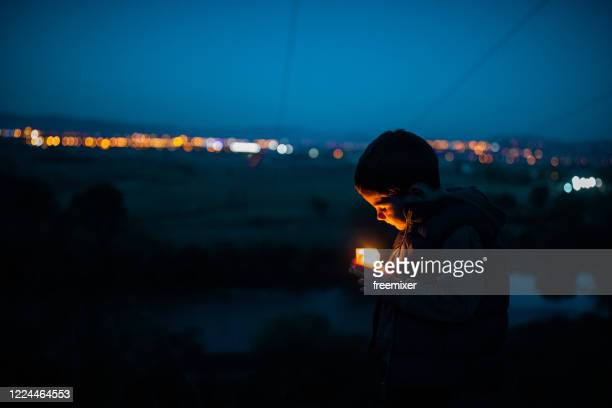 cute boy standing near river with candle at night - candle stock pictures, royalty-free photos & images