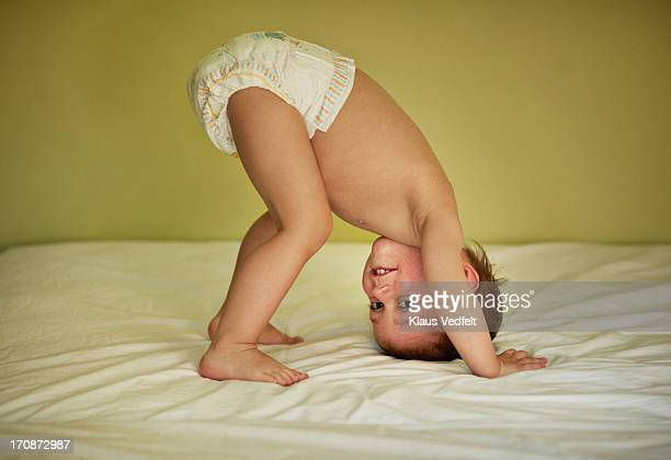 cute boy standing on his head - diaper boy stock photos and pictures