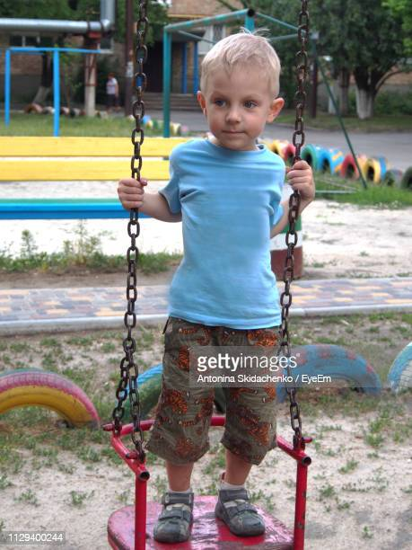 Cute Boy Standing On Swing In Playground