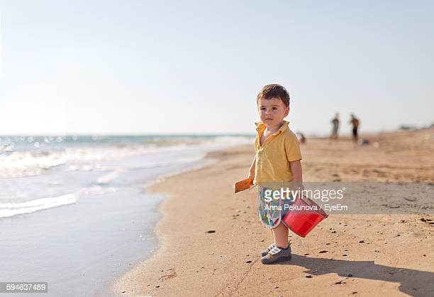 Cute Boy Standing While Carrying Bucket At Beach