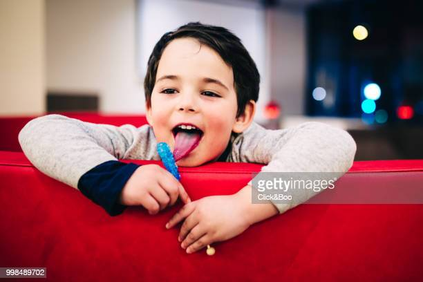 Cute boy sticking his tongue out eating a lollipop (indoors)