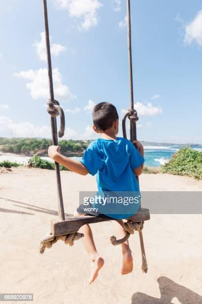 Chico lindo al aire libre de balanceo