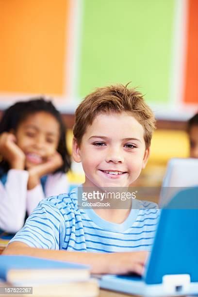 Niño atractivo usando una computadora portátil en su escuela