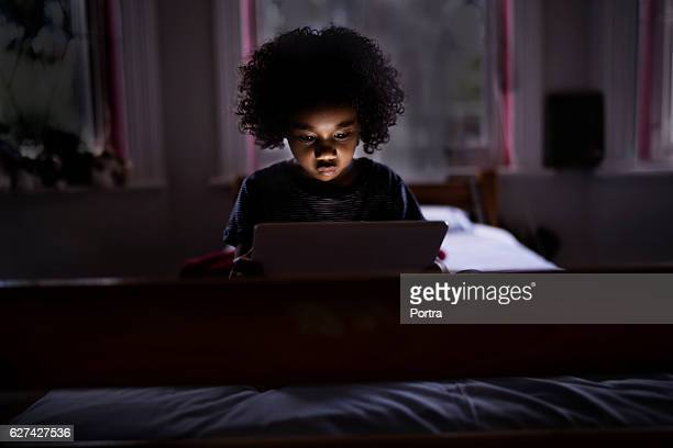 Cute boy using digital tablet in dark bedroom