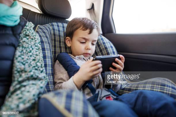 Cute boy using smart phone in car