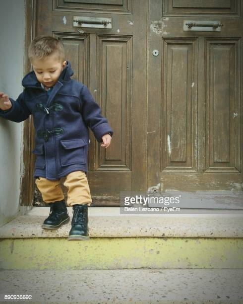 Cute Boy Walking On Steps Closed Door