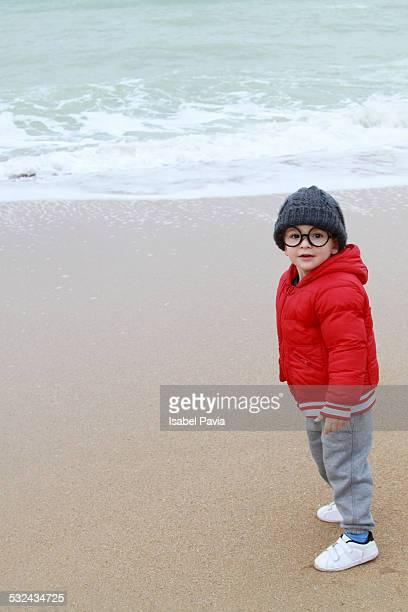 Cute boy walking on the beach in winter
