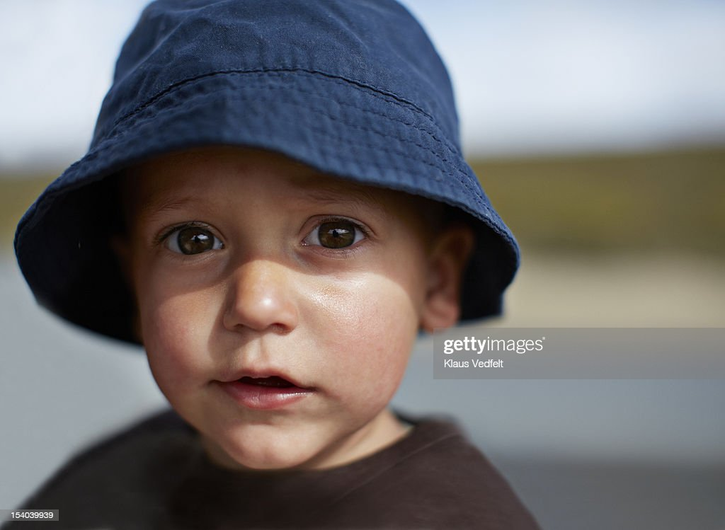 Cute boy with big eyes and hat, looking in camera : Stock Photo