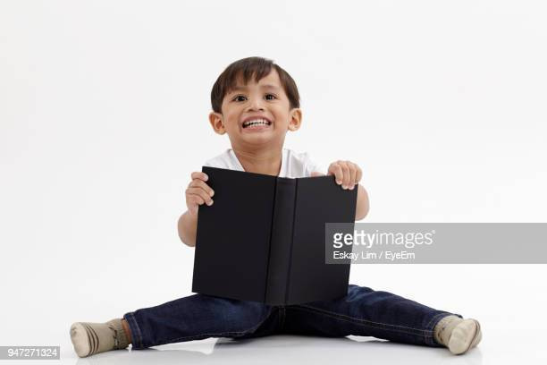 cute boy with book sitting against white background - legs spread open stock photos and pictures