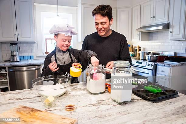 Carino ragazzo con sindrome di Down Cuocere al forno con papà a casa