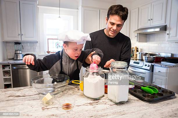 Cute boy with Down Syndrome baking with dad.