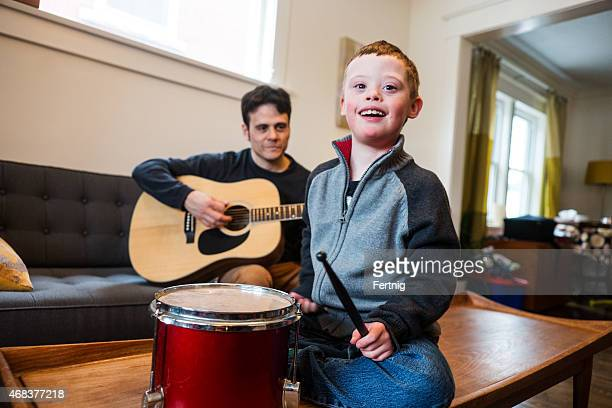 Cute boy with Down Syndrome playing music with dad.