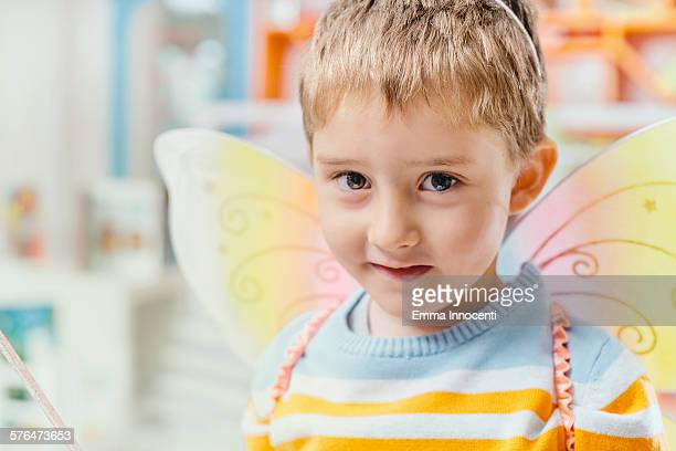 cute boy with fairy butterfly wing in classroom